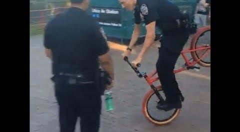 A Cop Doing A Hang Five On A BMX Bike