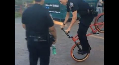 A Cop Doing A Hang Five On A BMX Bike